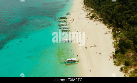 Coast with sandy beach with tourists and clear blue sea top view, Puka shell beach. Boracay, Philippines. Seascape with beach on tropical island. Summer and travel vacation concept.