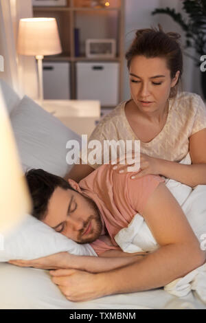 woman wakes her sleeping husband up in bed at home - Stock Photo