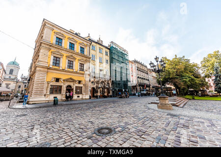 Lviv, Ukraine - August 1, 2018: Dominican church in historic Ukrainian Polish Lvov city during day on cobblestone street and wide angle view of yellow - Stock Photo