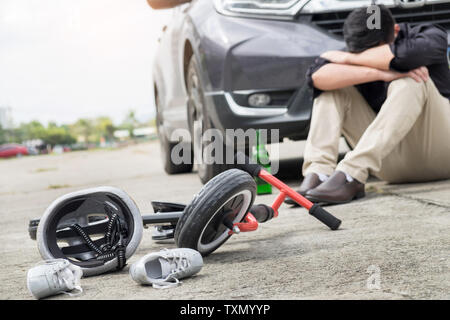 scared and stressed desperate drunken driver and bottle of beer in front of automobile crash car with child bike after traffic accident in city road - Stock Photo