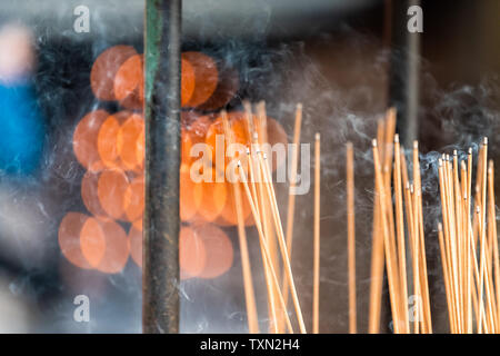 Kyoto, Japan temple shrine incense smoke burning flame sticks closeup with red orange bokeh background and nobody