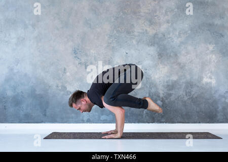Sporty young man working out, doing handstand yoga asana, Crow Pose or Bakasana - Stock Photo