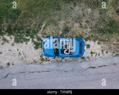 Overhead view of friends talking inside car by roadside - Stock Photo