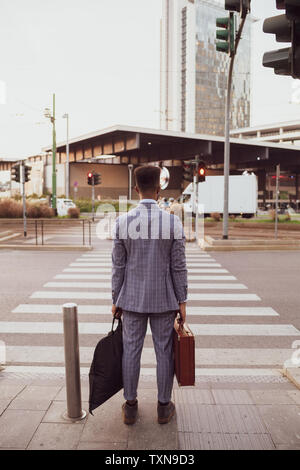 Businessman waiting by pedestrian crossing, Milano, Lombardia, Italy - Stock Photo