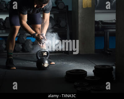 Man powdering hands before lifting kettlebell in gym - Stock Photo