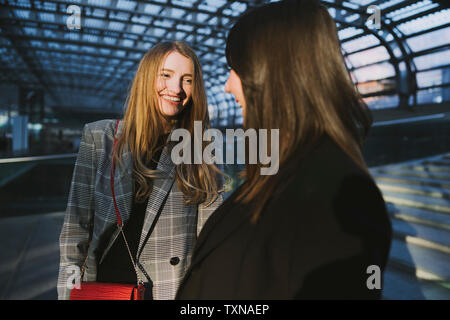 Two young women chatting on stairway in train station, Turin, Piemonte, Italy - Stock Photo