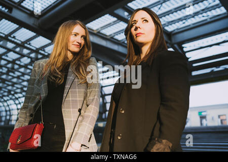 Two young women on stairway in train station, Turin, Piemonte, Italy - Stock Photo