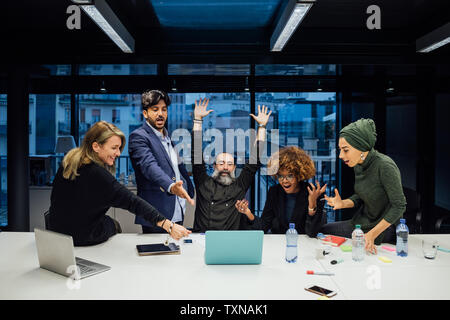 Business partners rejoicing in office - Stock Photo