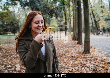 Young woman with long red hair taking smartphone selfie in autumn park