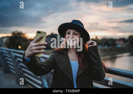 Young woman with long red hair on footbridge taking smartphone selfie at dusk, Florence, Tuscany, Italy
