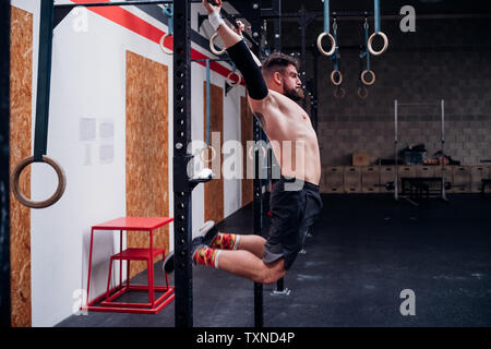 Bare chested young man training, swinging on exercise bar in gym - Stock Photo