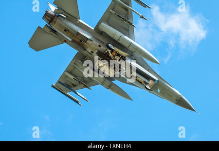 Dutch F-16 fighter plane taking part in NATO exercise Frysian flag, low angle against blue sky, Netherlands - Stock Photo