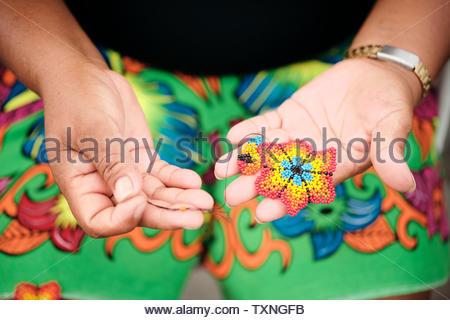 Indigenous woman beading flower coaster, Ciudad de Panamá, Panama - Stock Photo