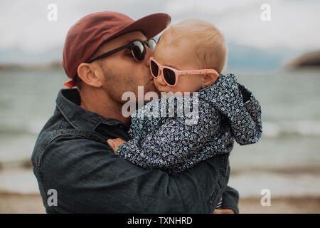 Father kissing baby on beach - Stock Photo