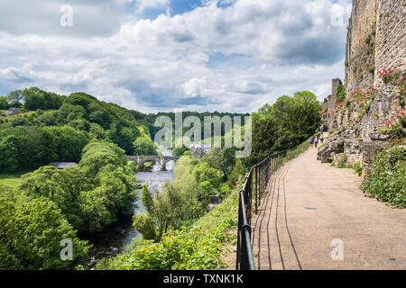 Richmond Castle walls and the Castle Walk footpath above the River Swale in in Yorkshire Dale country North Yorkshire - Stock Photo