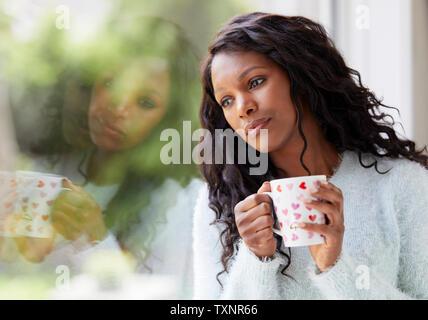 Ethnic woman looking sad sat in a window