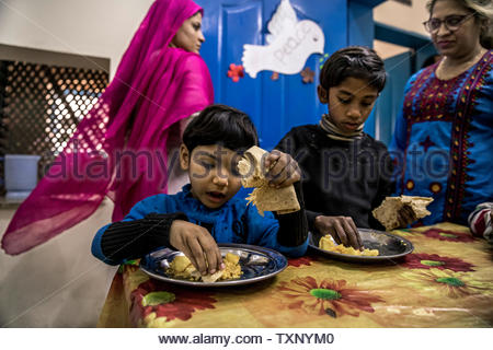 Orphans at lunch in an Christian orphanage with school in the largest Christian quarter Youhanabad, Lahore, Punjab, Pakistan. - Stock Photo