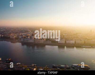 Aerial view of Hungarian Parliament Building in Budapest from above with Danube river and next to St-Stephans-Basilika during sunrise (Budapest) - Stock Photo