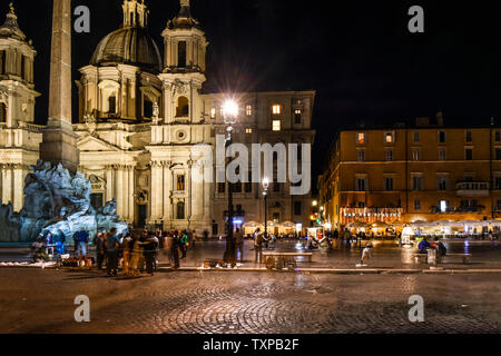 Late night on the Piazza Navona, with the Fountain of Four Rivers and sidewalk cafes illuminated by the Sant'Agnese in Agone church, in Rome, Italy - Stock Photo