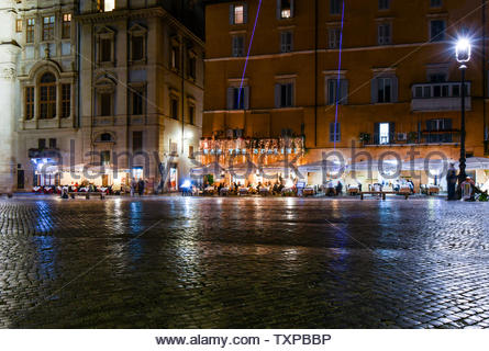 An illuminated restaurant sidewalk cafe late night on the Piazza Navona in Rome, Italy - Stock Photo