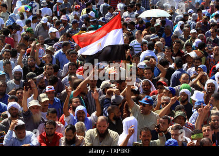 Supporters of deposed Egyptian President Mohamed Morsi as they shout slogans during a protest outside Raba El-Adwyia mosque in Cairo in Egypt, July 27, 2013. Dozens of people have been killed in overnight clashes between security forces and supporters of ousted Egyptian President Mohammed Morsi. UPI/Ahmed Jomaa - Stock Photo