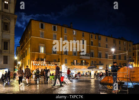 Late night on the Piazza Navona as tourists and street artists mingle in from of shops and sidewalk cafes in Rome, Italy. - Stock Photo