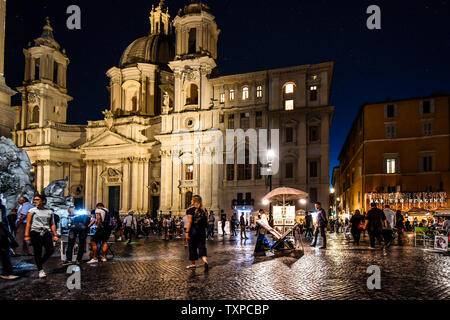 Late night on the colorful illuminated Piazza Navona, filled with tourists, street artists and vendors selling souvenirs, in Rome, Italy. - Stock Photo