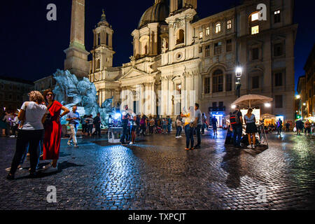 Late night on the Piazza Navona in Rome Italy as tourists and local Italians enjoy the lively atmosphere, illuminated fountains and street artists. - Stock Photo