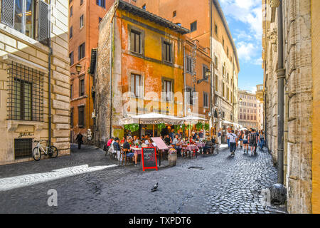 Tourists enjoy lunch on a summer day at an Italian sidewalk cafe restaurant in an alley near the historic center of Rome, Italy. - Stock Photo