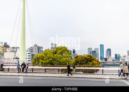 Osaka, Japan - April 13, 2019: Tenma bridge in spring with water view cityscape of downtown and people walking crossing on pedestrian sidewalk - Stock Photo