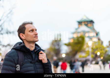 Osaka, Japan castle grounds in evening with people man tourist standing by building at night bokeh background - Stock Photo
