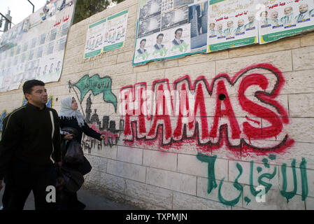 Palestinians walk past a wall plastered with campaign posters and Hamas graffiti for candidates for the Palestinian legislative election in Gaza January 3, 2006, in Gaza City, Gaza Strip. The official start of campaigning for the upcoming legislative elections in the Palestinian territories was at midnight.   (UPI Photo/Ismael Mohamad) - Stock Photo
