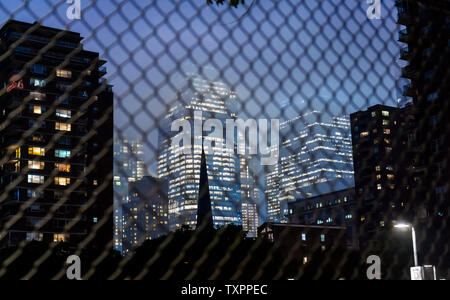 Hudson Yards in New York is seen through a chicken wire fence at night on Tuesday, June 18, 2019. (© Richard B. Levine) - Stock Photo