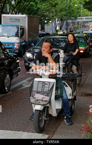 TOKYO, JAPAN, May 10, 2019 : Man waiting in the traffic on a bike, smoking a cigarette. - Stock Photo