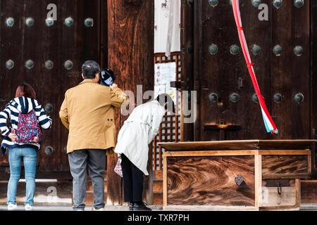 Nara, Japan - April 14, 2019: People bowing at Kofuku-ji temple in city with banner - Stock Photo