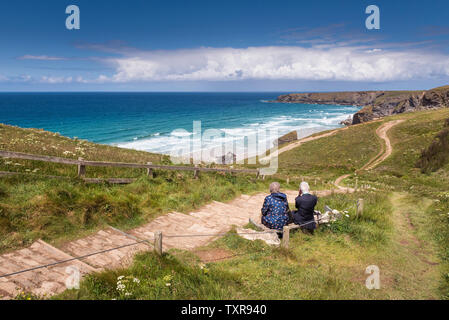 A mature couple sitting on a bench and enjoying the view over the rugged, spectacular coastline at Carnewas and Bedruthan Steps on the North Cornwall - Stock Photo