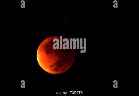 Super moon, appearing in a dim red colour, is covered by the Earth's shadow during a total lunar eclipse  as seen in Gaza September 28, 2015. were treated when the shadow of Earth cast a reddish glow on the moon, the result of rare combination of an eclipse with the closest full moon of the year. lunar eclipse, also known as a 'red Moon' is one that appears bigger and brighter than usual as it reaches the point in its orbit that is closest to Earth. Photo by Ismael Mohamad/UPI - Stock Photo