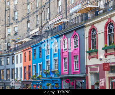 Facades of ancient stone buildings, with people on Victoria Terrace above the colourful shopfronts in historic Victoria Street, Edinburgh Old Town. - Stock Photo