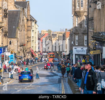 Busy street scene on Canongate, part of the Royal Mile, with fine architecture in warm April sunshine. Edinburgh city centre, Scotland, UK. - Stock Photo