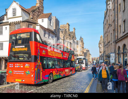 City sightseeing open top tour bus and a busy street scene on Canongate, part of the Royal Mile,  in warm April sunshine. Edinburgh, Scotland, UK. - Stock Photo
