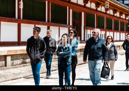 Nara, Japan - April 14, 2019: People tourist group family walking by Todaji temple in city during day - Stock Photo