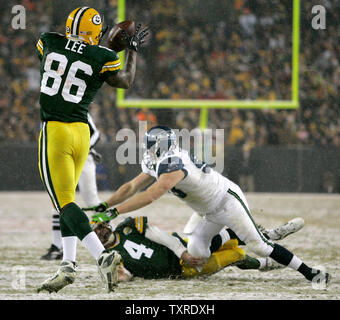 Green Bay Packers quarterback Brett Favre (4) is leveled by Seattle Seahawks defensive tackle Craig Terrill (R) after completing an 11-yard reception to tight end Donald Lee (86) during the second quarter of the NFC Divisional Playoff at Lambeau Field in Green Bay, Wisconsin on January, 12, 2008. The Packers won 42-20. (UPI Photo/Brian Kersey) - Stock Photo