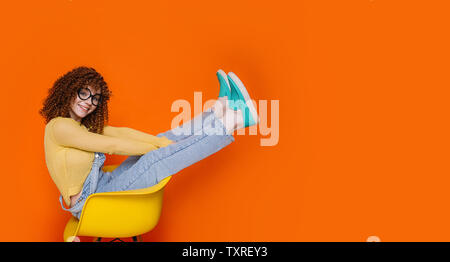 Trendy teenage with curly hair wearing denim overalls and yellow jacket sitting on chair with raised legs. funny young woman on orange background - Stock Photo