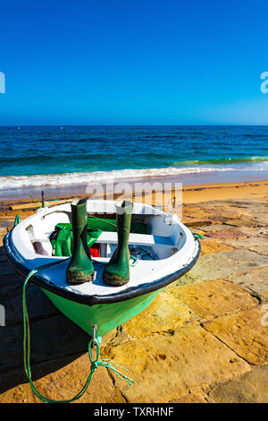 Green wellies on a green boat, Algarve, Portugal - Stock Photo