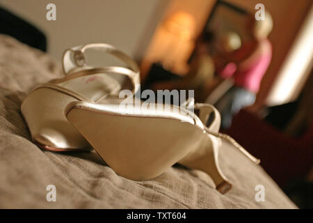 Bride's gold coloured wedding dress shoes on bed - Stock Photo