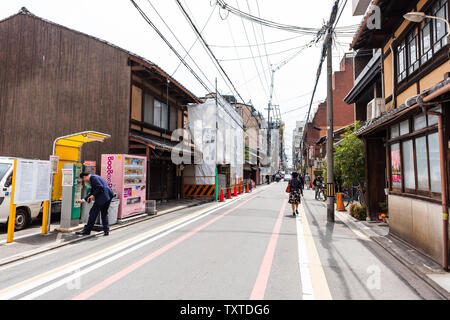 Kyoto, Japan - April 17, 2019: City street in downtown with man buying from vending machine and local people walking