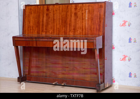 Old wooden piano keys on wooden musical instrument in front view . Old wooden piano. Brown piano stands against the wall .