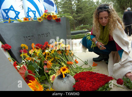 An Israeli places flowers at the grave of the late Israeli Prime Minister Yitzhak Rabin  on Mt. Herzl in Jerusalem, November 4, 2005. Today marks the 10 year anniversary of the assassination of Prime Minister Yitzhak  Rabin by a Jewish extremist after a peace rally in Tel Aviv on November 4, 1995,  for his political policy of land for peace with the Palestinians. (UPI Photo/Debbie Hill) - Stock Photo