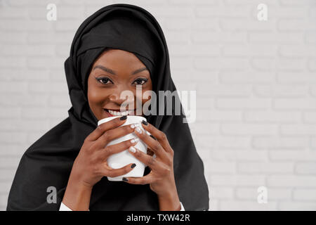 Beautiful, charming muslim woman holding white cup, with perfect smile looking at camera. Pretty, young, stylish african girl with black and white manicure wearing black hijab. - Stock Photo