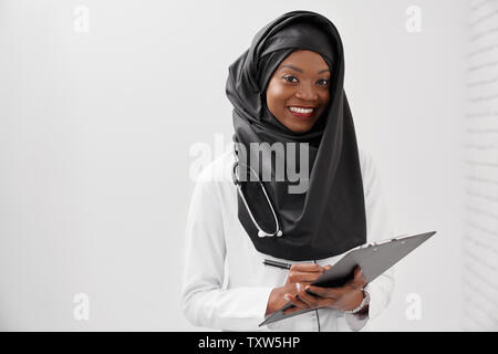 Beautiful, positive female doctor with stethoscope holding folder and pen, looking at camera. Cheerful woman wearing in black hijab and white coat writing and smiling.